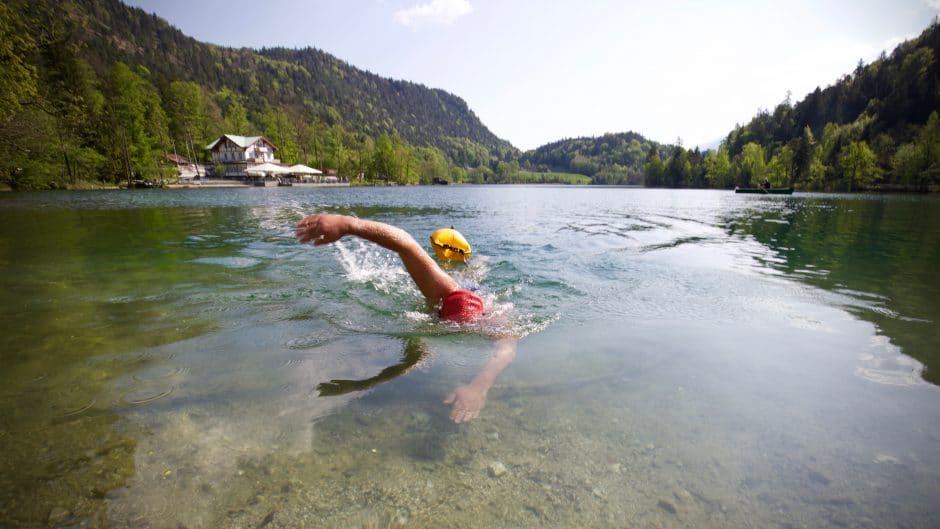 Im Vordergrund steht am Thumsee das Wild Swimming Vergnügen - im Hintergrund sieht man den denkmalgeschützten Seewirt.